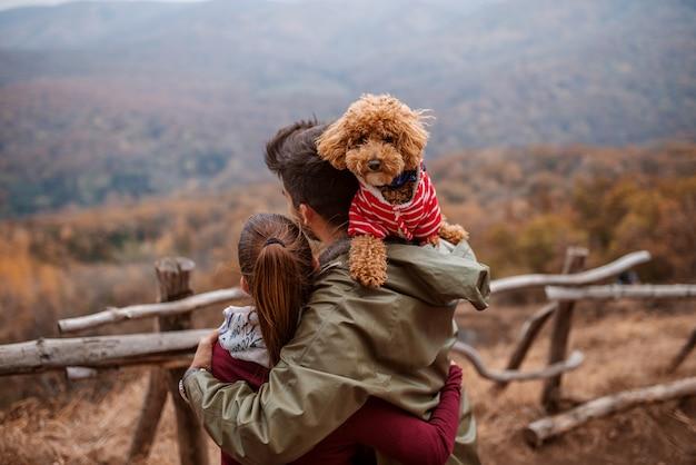 Paar knuffelen en kijken naar adembenemend uitzicht.
