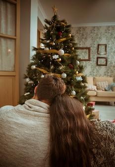 Paar knuffelen en kijken naar de kerstboom