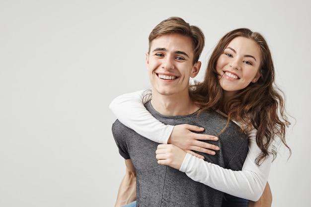 Paar knuffelen en lachen in de buurt van de muur.