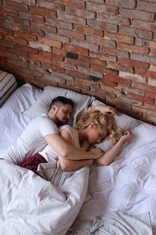 Paar knuffelen en slapen in het bed