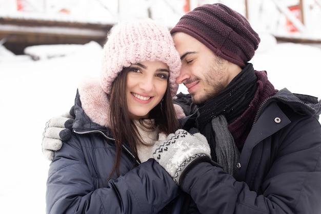 Paar knuffelen en zoenen in het park in de winter.