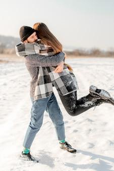 Paar knuffelen in de sneeuw
