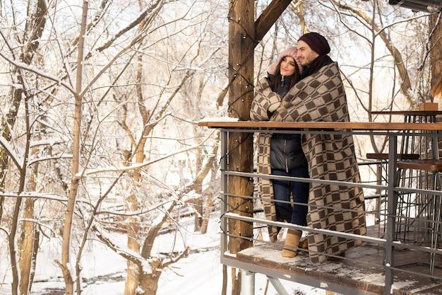 Paar knuffelen in het park in wintercafé