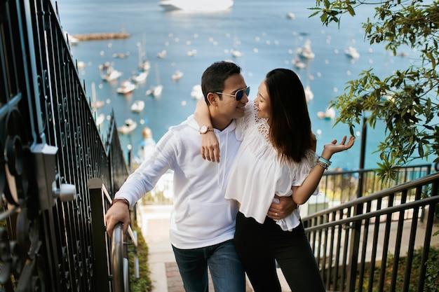 Paar knuffelen op de trap met uitzicht op de oceaan, indiase brunette man knuffel aziatisch meisje.