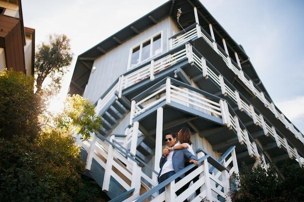 Paar knuffelen op de trap van groot huis, indiase brunette man knuffel aziatisch meisje. date jonge mensen bij zonnig weer.