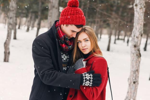 Paar knuffelen op een besneeuwde veld
