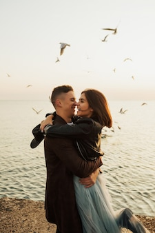 Paar knuffelen op het strand en man die de vrouw opheft.