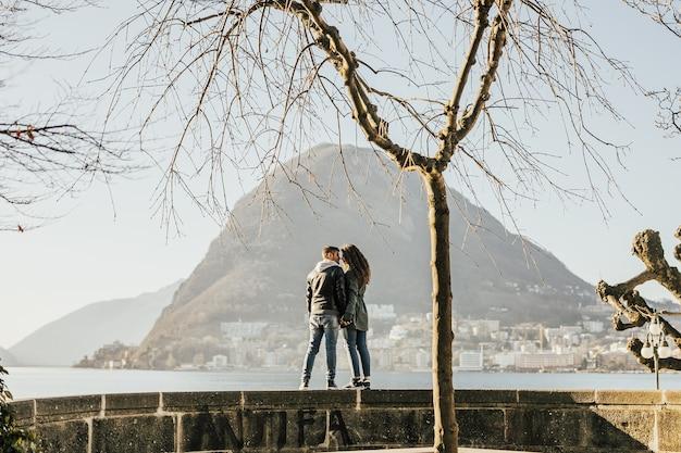 Paar knuffelen verliefd staande aan de oever van het meer van lugano, zwitserland.
