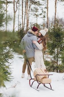 Paar knuffels en kusjes in een winter naaldbos en draagt dozen met geschenken op een slee