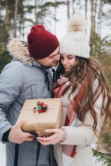 Paar knuffels en kusjes in een winter naaldbos, geef elkaar dozen met cadeaus