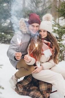 Paar knuffels en verbrandt sterretjes in een winter naaldbos zittend op een slee