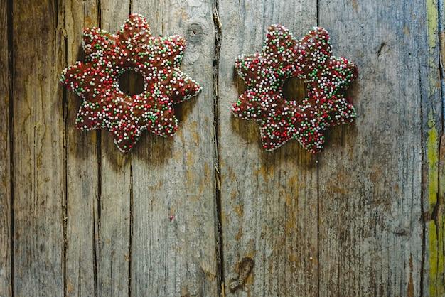 Paar koekjes gedompeld in chocolade en toppings in de vorm van een kerstster.