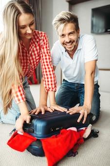 Paar koffer inpakken voor vakantie, overvol