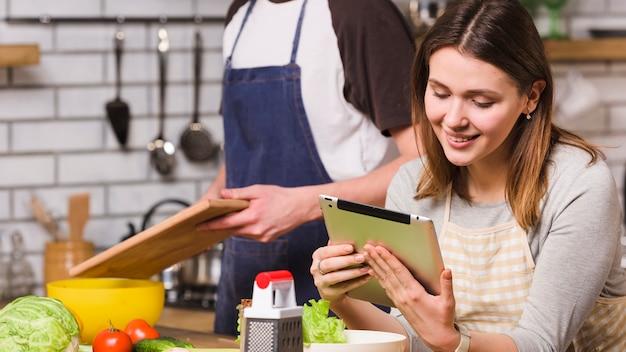Paar kokend voedsel die tablet gebruiken