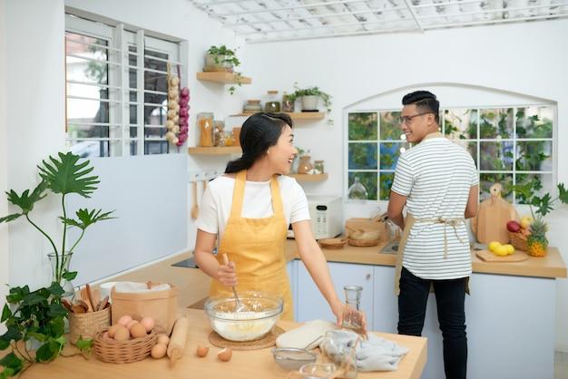 Paar kokende bakkerij in keukenruimte, jonge aziatische man en vrouw die samen cake en brood met ei maken,