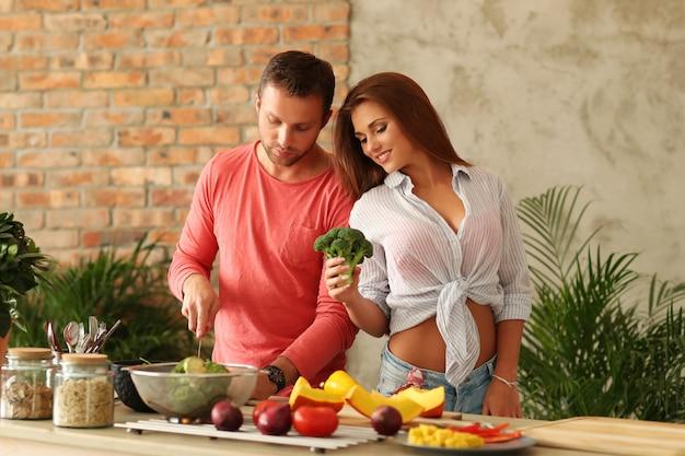 Paar kokende groenten in keuken
