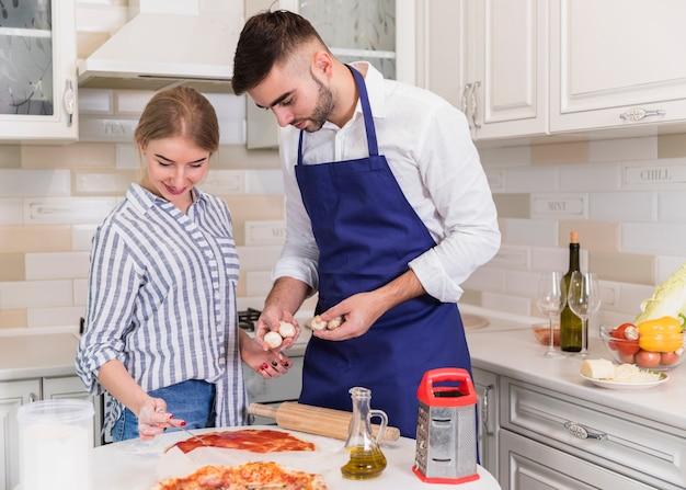 Paar kokende pizza in keuken