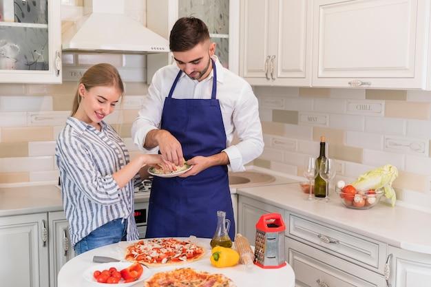 Paar kokende pizza met kaas in keuken