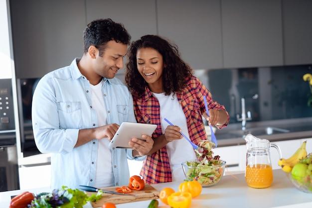 Paar kokende salade en het gebruiken van tablet op keuken