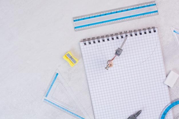 Paar kompassen die cirkel op papier tekenen