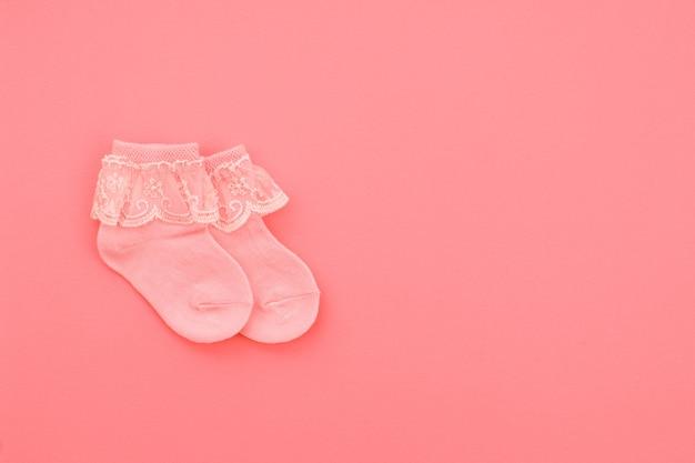 Paar koraal schattige baby sokken op koraal achtergrond. accessoires voor baby's. plat leggen.