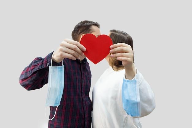 Paar kus en neemt beschermend medisch masker van gezichten af. overwinning op coronavirus. het einde van covid-19 pandemische crisis en lockdown.