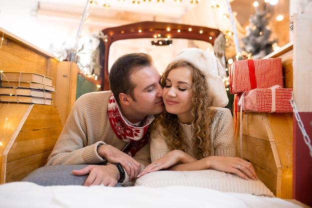 Paar kussen en genieten van hun tijd samen in pick-up auto. kerstverlichting op de achtergrond.