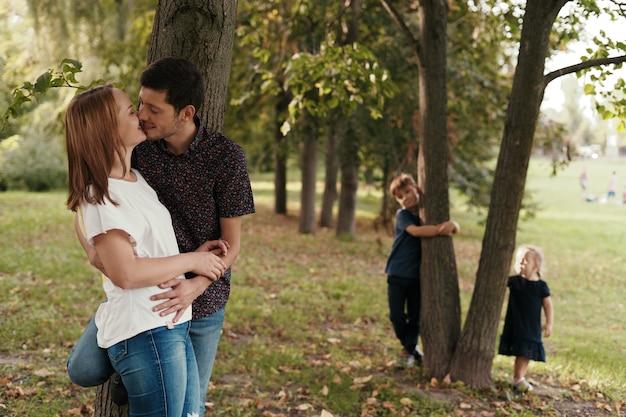 Paar kussen terwijl hun kinderen buitenshuis kijken