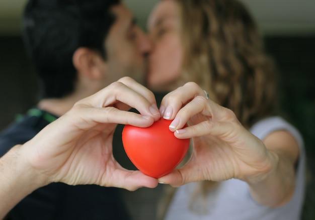 Paar kussen terwijl rood hart met handen vasthoudt