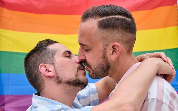 Paar kussende mannen achter een trotsvlag