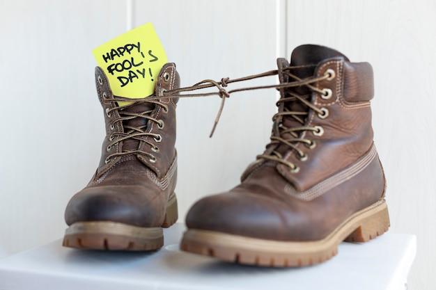 Paar laarzen met veters aan elkaar gebonden met een briefje met de zin happy fool's day.