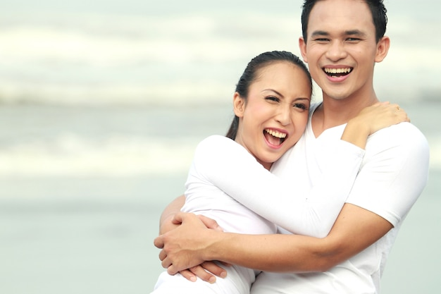 Paar lachen genieten van een zomervakantie op het strand