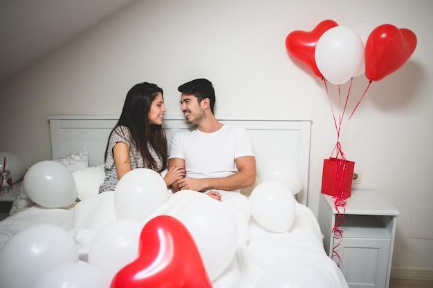 Paar lachen liggend op het bed met ballonnen om hen heen