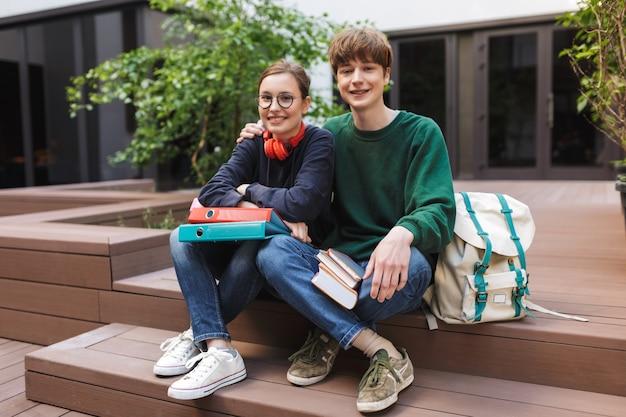 Paar lachende studenten zitten met mappen en boeken in handen en gelukkig l op de binnenplaats van de universiteit
