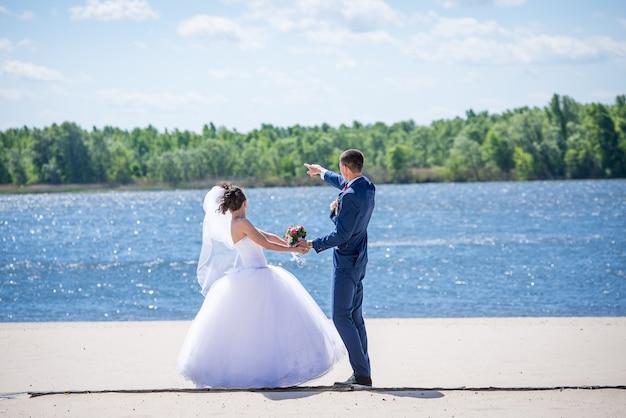 Paar legden hun handen op een bruidsboeket. mooi bruidsboeket. handen jonggehuwden met ringen.