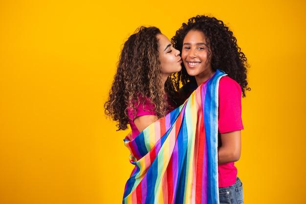 Paar lesbische vrouw met gay pride-vlag op gele achtergrond