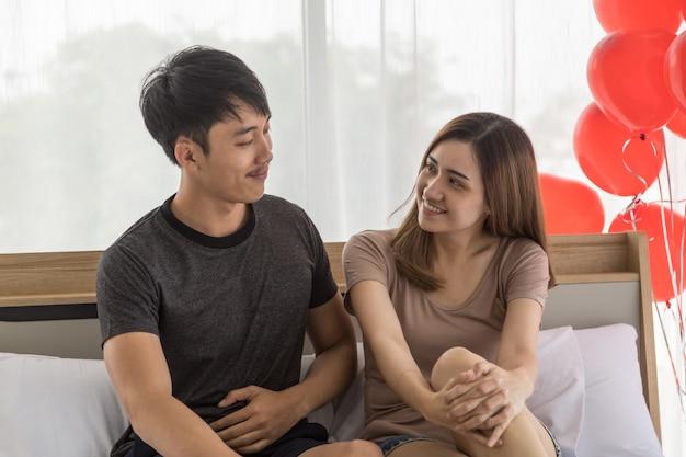 Paar, liefde en valentijnsdag concept. het portret van glimlachende aziatische man twee en vrouw die op elkaar kijken zien onder ogen en zitten op bed in slaapkamer met rode ballon.
