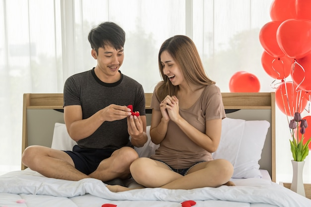 Paar, liefde en valentijnsdag concept. portret van twee glimlachende aziatische man verrassingsvrouw met gouden ringszitting op bed in slaapkamer met rode ballon.