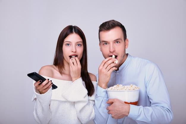 Paar liefhebbers eten karamel of gezouten popcorn met voortekenen tijdens het kijken naar film thuis theater