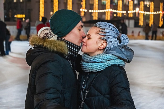Paar liefhebbers knuffelen en kussen op de ijsbaan op valentijnsdag of kerstmis.