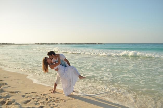 Paar liefhebbers kussen op het strand van het caribisch gebied