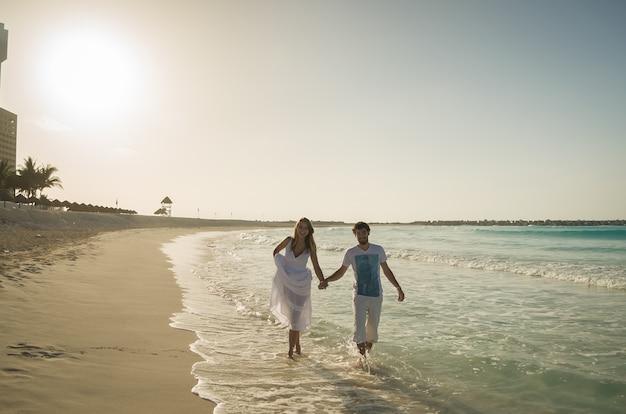 Paar liefhebbers lopen hand in hand op caribisch strand bij zonsondergang