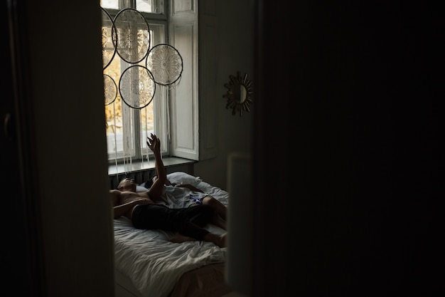 Paar liefhebbers ontspannen op het bed in de ochtend. ze hielden elkaars hand vast. donker interieur.
