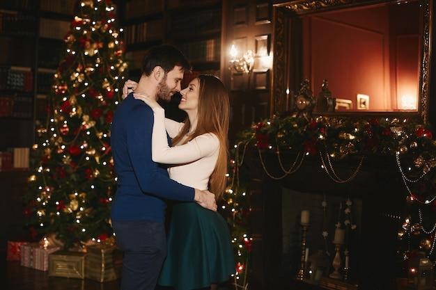 Paar liefhebbers poseren in de buurt van de kerstboom