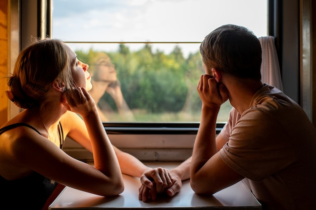 Paar liefhebbers reizen in de trein. stemmingsportret van het houden van van romantisch paar in wagen die venster met zelfbezinningen daarin bekijken. avontuur op vakantie van gelukkige familie.