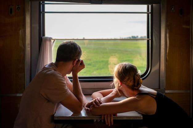 Paar liefhebbers reizen in de trein. stemmingsportret van het houden van van romantisch paar in wagen die venster met zelfbezinningen daarin bekijken.