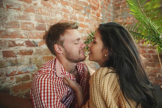 Paar liefhebbers thuis samen ontspannen. blanke man en vrouw die weekend hebben, ziet er teder en gelukkig uit. concept van relaties, familie, herfst- en wintercomfort. gepassioneerd voor elkaar.