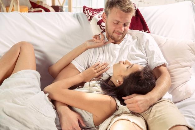 Paar liefhebbers thuis samen ontspannen. blanke man en vrouw die weekend hebben, ziet er teder en gelukkig uit