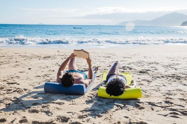 Paar liggen en lezen op het strand
