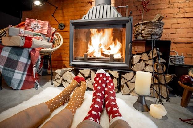Paar liggend bij de brandende open haard ingericht voor de nieuwjaarsvakantie in een gezellig huisinterieur